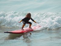 Peque in red surfboard
