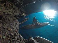 Seduta sul tabellone all'interno della grotta