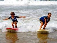 ninos surf tomando olas