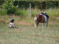 Peque sentado junto al caballo