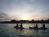Remando a bordo de kayaks dobles al anochecer