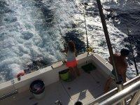 Ragazza che pesca dalla barca