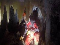 Explorador de cuevas tras estalagtita