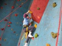 Nina arrampicata su una parete di roccia