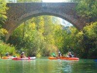Grupo de piraguistas bajo un puente
