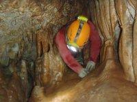Hombre metiendose en las cuevas con su casco encendido