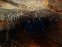 Tres personas saludan a camara dentro de la cueva