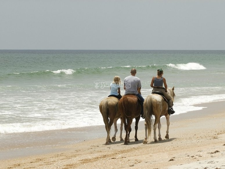 En familia a caballo en la playa