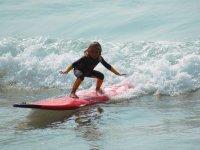 Piccola sulla tavola da surf rossa