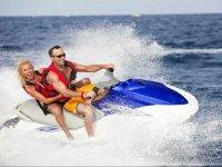 Pareja con chalecos salvavidas en moto de agua