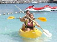 Chicas en kayak con motos de agua detras