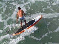 Haciendo paddle surf sobre las olas