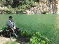 Pescador sentado en la ribera