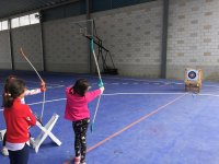 Children aiming with the bow at the target