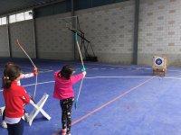 Niños apuntando con el arco a la diana